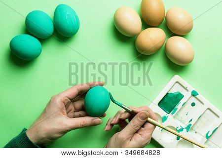 Girl's Hands Paint Colored Easter Eggs. Colored Easter Eggs With Feathers On A Green Background. Mon