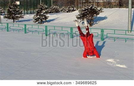 Handstand In The Snow, A Child Doing Sports In The Snow, A Girl In A Red Jacket And A Red Hat With E