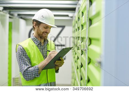 Smiling Young Manual Worker In Protective Workwear Making Notes In Document While Standing In Front