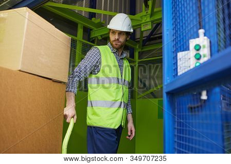 Young Worker In Protective Workwear Carrying Boxes On Cart While Working In Stockroom
