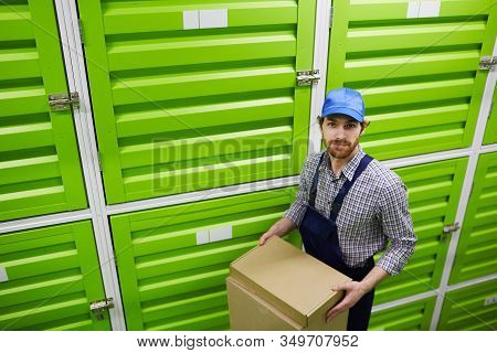 Portrait Of Young Man In Cap And In Overalls Holding Box And Looking At Camera While Standing Near T