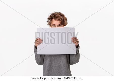 Pretty Young Woman Holding Empty Blank Paper Board With Copy Space For Text.
