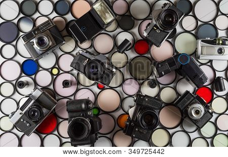 Vintage Film Camera And Flashes Lie On A Background Of Multi-colored Glass Photographic Filters Of V