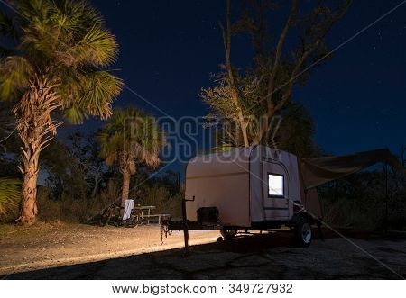 Small teardrop trailer at a campsite at night with stars.