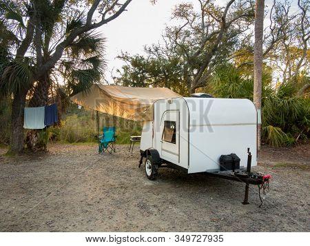 Teardrop camper camped in tropical location at sunrise.