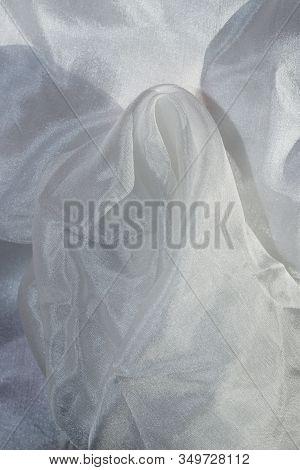 Blurred Background Crumpled White Fabric. Abstract White Textile Texture Background. Fabric Folds.