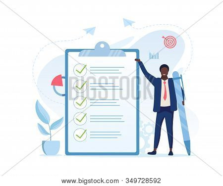 Fulfilment Of Business Tasks Concept With A Businessman Holding A Large Pen Standing Alongside A Cli