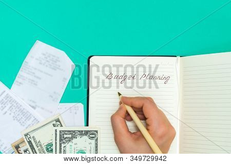 Top View Of Receipts And Cash And Woman Hand Writing In A Notepad Words Budget Planning. Personal Bu