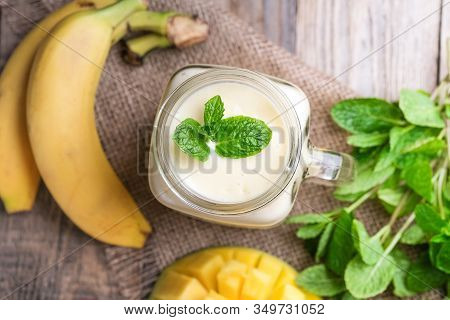 Delicious Mango Smoothie In Mason Jar On A Rustic Background. Healthy Food, Detox Diet. Copy Space.
