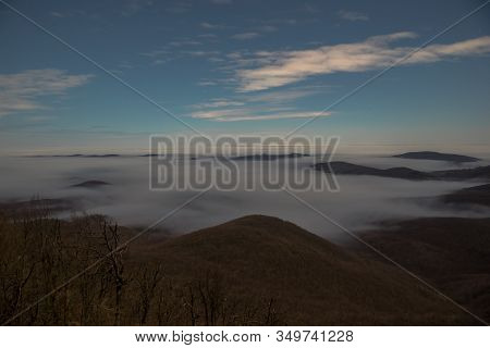 Inverse Clouds Lie In The Valleys Between The Mountains At Moonlight