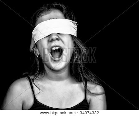 Black and white image of a small girl screaming and blindfolded with a handkerchief isolated on black with space for text