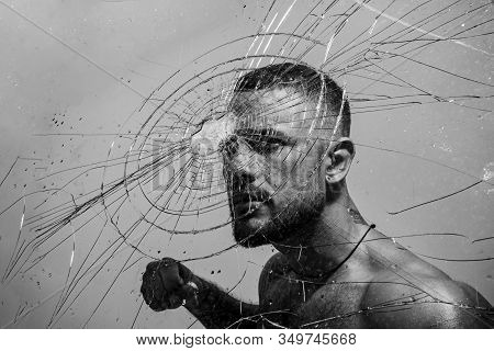 Muscular Man Having Inner Determination And Commitment To Break Glass Wall. Determined Latino Man Re