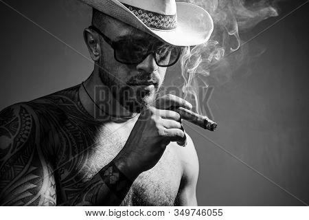 Cuban Cigars. Portrait Of Latin Face With A Sensual Look. Cuban Man Smoking Cigar And Enjoy Life And