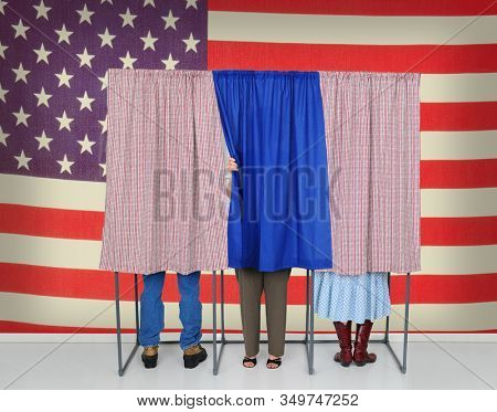 Three Voting booths in front of a large American Flag. Two Women and one male behind curtains, one woman is starting to leave.