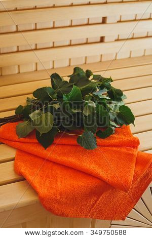 The Bath Broom With An Orange Towel Lies On A Bench In A Sauna