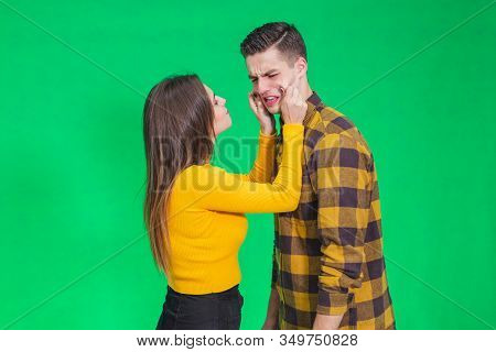Girl Pinching Guys Cheeks, Making Fyn, He Is Scowling His Face, Looking Completely Annoyed.
