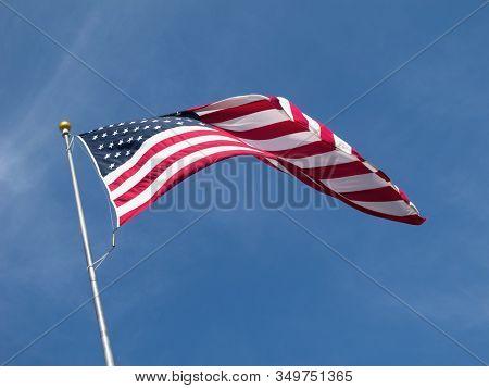 In A Brisk Breeze A Sunlit Flag Of The United States Of America Flies High.in A Brisk Breeze A Sunli