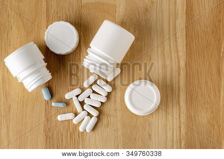 A Medical Set-up. Plastic White And Glass Bottles. Medicinal Blue And White Pills.