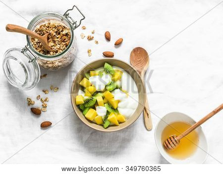 Greek Natural Yogurt With Tropical Fruits And Granola On A Light Background, Top View. Natural Yogur
