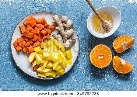 Ingredients For Vitamin Smoothies - Fresh Ripe Mango, Carrot, Orange, Honey, Ginger On A Blue Backgr