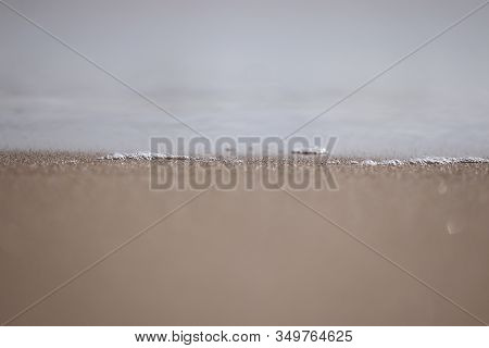 Close Up Of White Bubbles On Water Surface From Beach With Blur Sandy Background,water Surface  Back