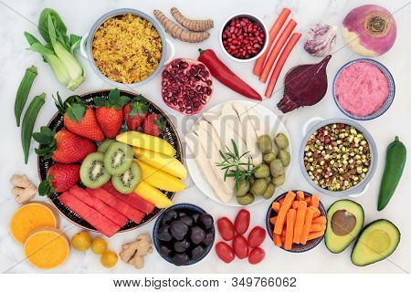 Health super food for fitness with foods high in antioxidants, anthocayanins, vitamins, minerals, protein, smart carbs, lycopenes, omega 3 and fiber. Flat lay on marble.