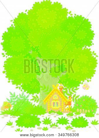 Small Wooden House From A Fairytale With Easter Decorations, A Porch And A Fence Under A Big Branchy