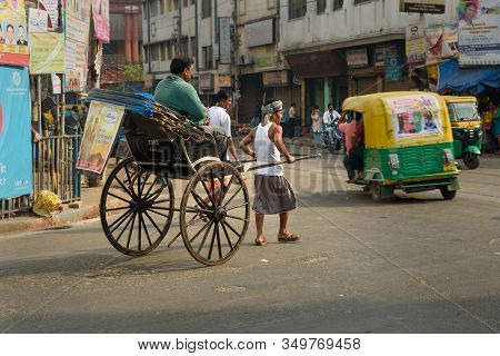 Kolkata, India - March 13, 2019: Man Rickshaw Puller Is Pulling His Hand Rickshaw With Passenger On