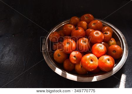 Fresh Harvested Sunkissed Ripe Red Tomatoes Kept In A Rustic Steel Plate In A Sunny Place In Kitchen
