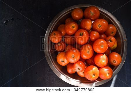 Fresh Harvested  Ripe Red Tomatoes Kept In A Rustic Steel Plate In A Sunny Place In Kitchen. Tomatoe