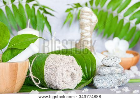 Closeup Of Wooden Mortar Pounder With Herbs, Herbal Massage Pouches, Towel, Bowl With Salt, Stones A