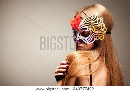 Seductive Woman In Large Multicolored Carnival Mask, Looking In Camera, Stroking Her Lower Lip With