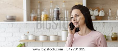 Always In Touch. Young Woman Talking On Cellphone At Kitchen Interior, Panorama, Free Space