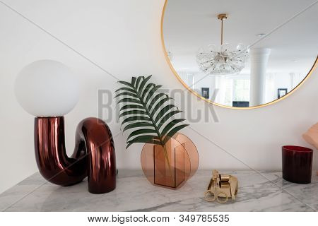 Stylish Composition Of Red Mirror Table Lamp With Gold Stationary On White Marble Top With Copy Spac