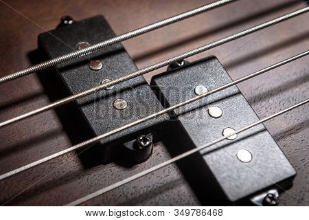 Bass Electric Guitar With Four Strings Closeup. Detail Of Popular Rock Musical Instrument. Close Vie