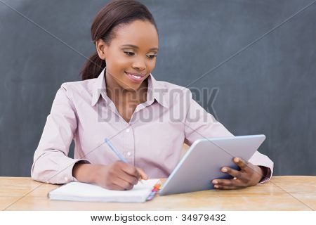 Teacher writing while looking at a tablet computer in a classroom