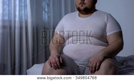 Fat Man Sitting On Bed, Weight Gain Due To Sedentary Lifestyle, Hormonal Disease