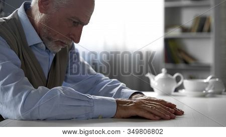 Lonely Retiree Gentleman Sitting At Kitchen Table, Old Male Suffering Loneliness