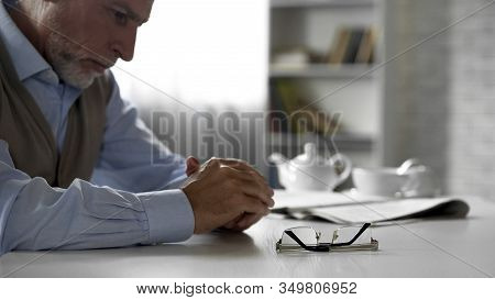 Retiree Male Sitting Alone At Kitchen Table Taken Off His Glasses, Poor Vision
