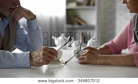 Elderly Couple Discussing Problem Sitting Across Table Over Cup Of Tea, Dispute