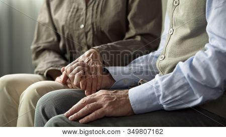 Retiree Male And Female Sitting On Sofa, Woman Holding Man Hand Support And Care