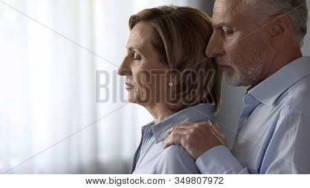 Sad Retiree Woman Standing By Window, Husband Comforting Her, Taken By Shoulders