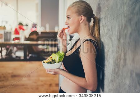 Beautiful Young Lady With Salad In The Gym. Sport Women Exercise With Healthy Food. Mental Health An