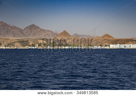 Sea Pier Near Sharm El Sheikh With Clear Blue Water, Green Palm Trees And The Sinai Mountains In The