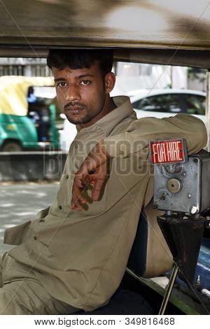Bengaluru, India - October 24, 2012. An Indian Tuk Tuk Driver Waits For A Fare In His Rickshaw, Beng