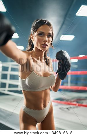 Front View Of Fit Brunette Woman With Open Mouth Wearing Boxing Gloves. Portrait Of Young Attractive