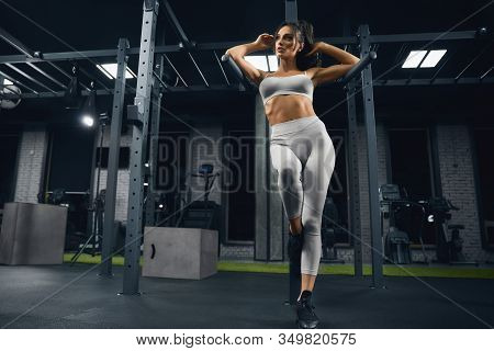 From Above View Of Female Bodybuilder In Beige Sportswear Posing Near Parallel Bars. Srtong Woman Wi