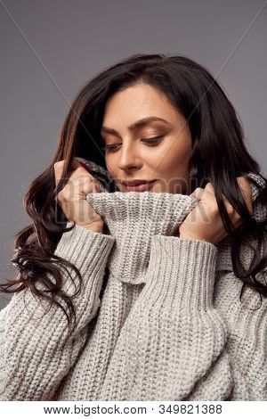 Portrait Of Fashionable Young Brunette Woman Posing In High Collar Knitted Sweater. Front View Of Se