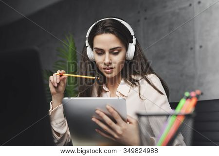 Girl In Headphones Learning Foreign Language Online. Young Female Listening To Music And Working On