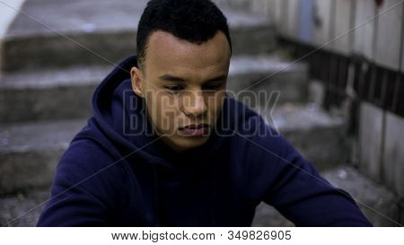 Hopeless Afro-american Teen Sitting On Steps In Ghetto, Concerned About Future
